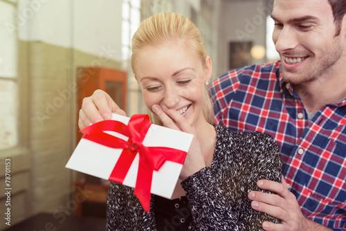 Leinwanddruck Bild junge frau freut sich über ein geschenk