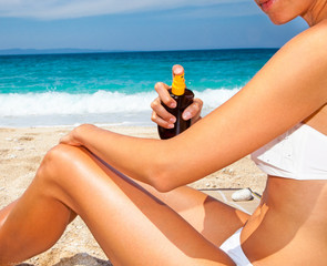 Woman applying suntan lotion from a spray bottle .