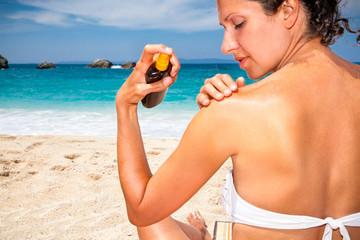 Woman applying suntan lotion from a spray bottle .