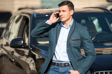 Young man with phone leaned on car