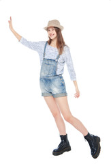 Young fashion girl in jeans overalls pushing something isolated