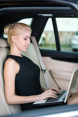 Smiling woman working on laptop inside car