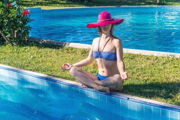 Woman meditating at the pool