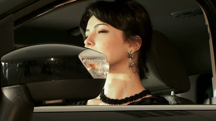 Beautiful Black-Haired Woman Sitting In Car