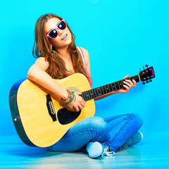 young woman sings and playing guitar