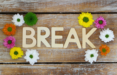 Break written with wooden letters and Santini flowers