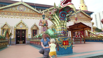 mother shows little blonde daughter dragon in Buddha temple