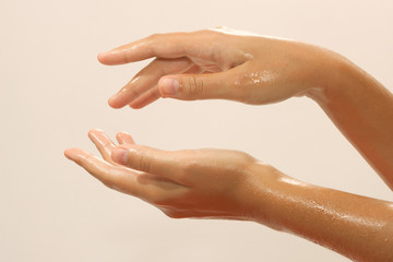 Close-up of female hands in oil on beige background