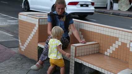 little blonde child plays with her mother on bench at pavement n
