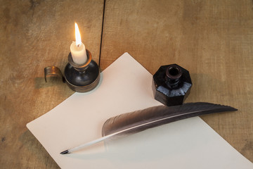 Quill pen and inkwell, and candlestick well resting on old paper
