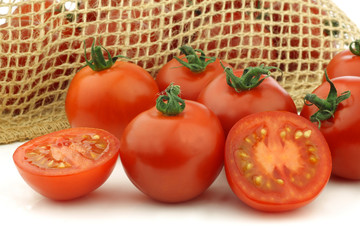 fresh tomatoes and a cut one on a white background