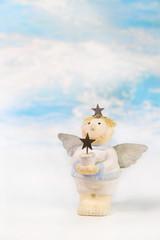 Weihnachtskarte: Engel mit einem Stern auf Hintergrund blau