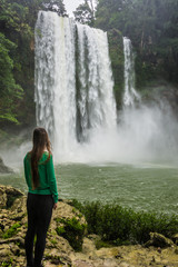 Girl looking at waterfall in motion, Beautiful Misol Ha, Chiapas