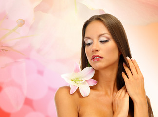 Beautiful young woman with lily flower on bright pink