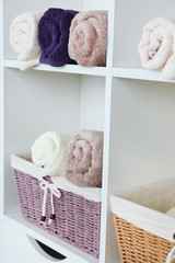 Rolled towels with wicker basket son shelf of rack background