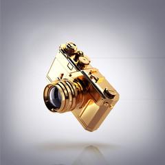 Golden photo camera on grey  background