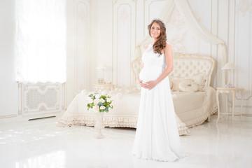 happy pregnant woman in a light interior