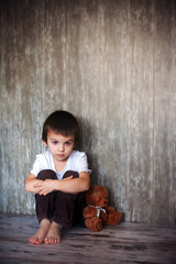 Young boy, sitting on the floor with his teddy bear