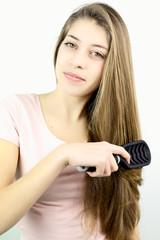 Teenager smiling while brushing long hair in studio