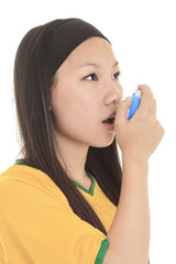 Close up image of a young woman using inhaler for asthma. White