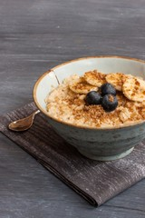 Oatmeal breakfast served with sliced bananas and berries