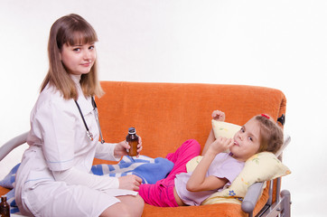 Doctor holding a medicine for little girl