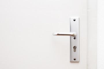 Sliver metallic door handle on the white wooden door close up