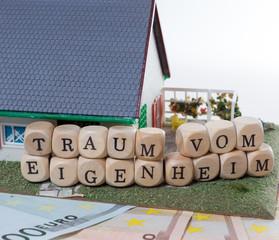 Geldscheine und Holzwürfel mit den Worten Traum vom Eigenheim