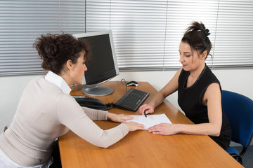 Business women having a meeting in the office sitting at a desk