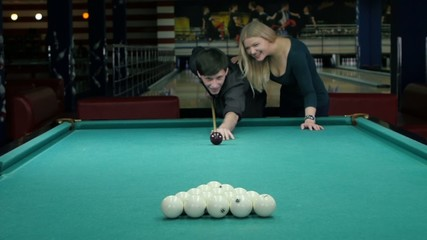 Happy couple playing pool. she supports her partner