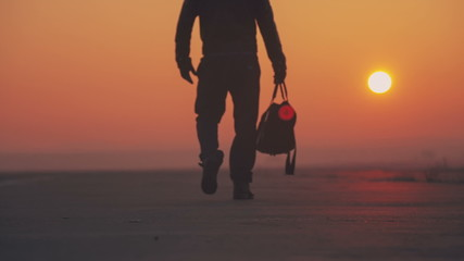 A man gets under way on a journey with a bag on the east
