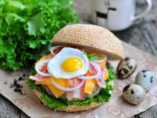 Hamburger with an egg, bacon, cheese and onion