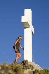 Mujer adulta haciendo senderismo junto a una cruz