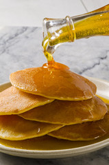 Agave syrup pouring on a plate of pancakes.