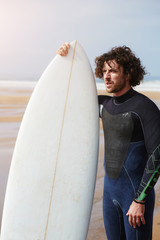 Professional surfer standing against the ocean holding surfboard