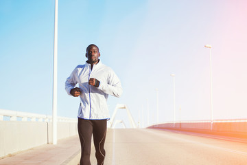Athletic black man running on a bridge road promenade outside