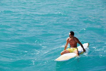 Mature man enjoying a surf at sunny day, surfer in the ocean