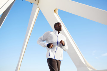 Dark skinned sporty man running over blue sky outdoors