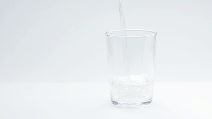 Water pour into a glass, white background