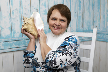 Old woman holding a seashell. Selective focus on her face. Blue