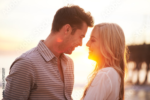romantic couple at sunset about to kiss - 78722517
