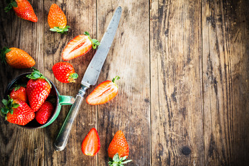 Ripe strawberries on the table next to the old knife.