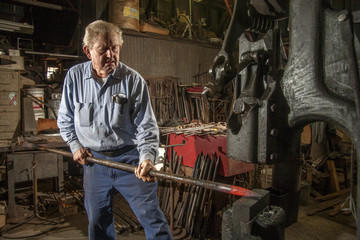 Elderly blacksmith pounds a red hot iron bar.