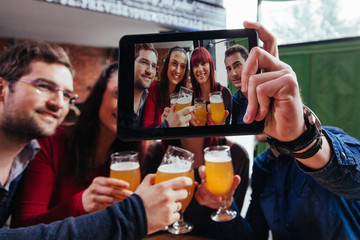 Group Of Friends In Tavern Taking Selfie