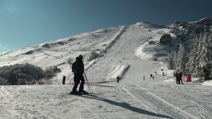 Ski resort in Stara Planina, ski slope with skiers and sun