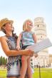 Mother and baby girl sightseeing near leaning tower of Pisa