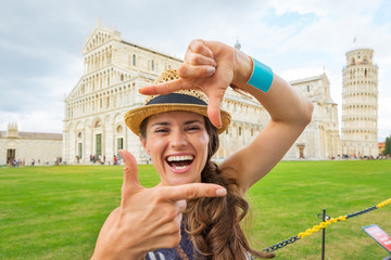 Portrait of happy woman framing on piazza dei miracoli, pisa