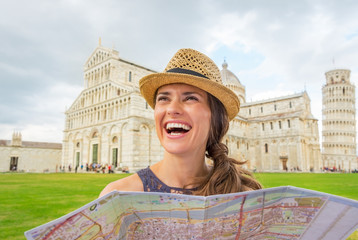 Smiling young woman with map on piazza dei miracoli, pisa