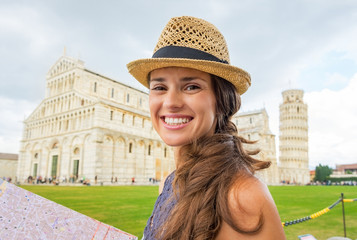 Portrait of happy woman with map on piazza dei miracoli, pisa