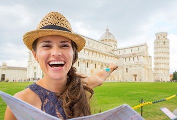 Happy young woman with map pointing on duomo di pisa, pisa